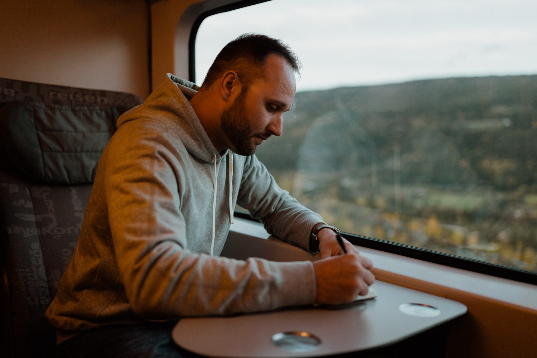 groom writes vows on train near window
