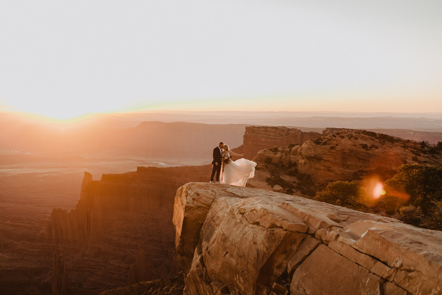 bride and groom kissing near edge of canyon