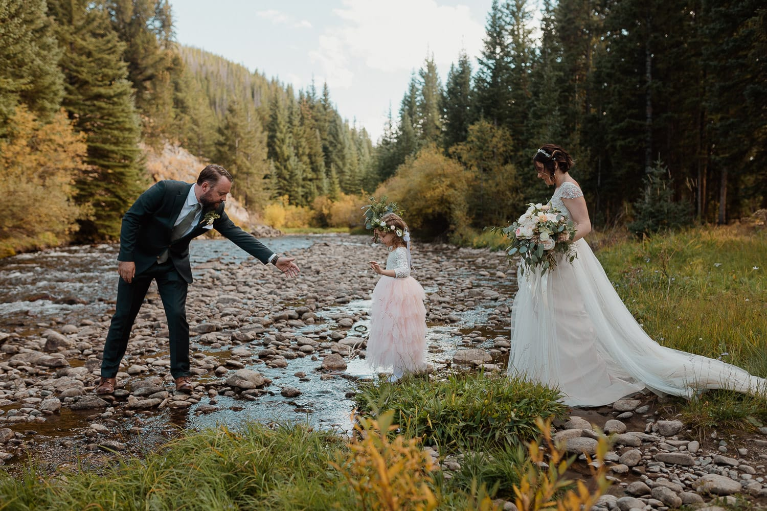 family crossing creek in forest on wedding day