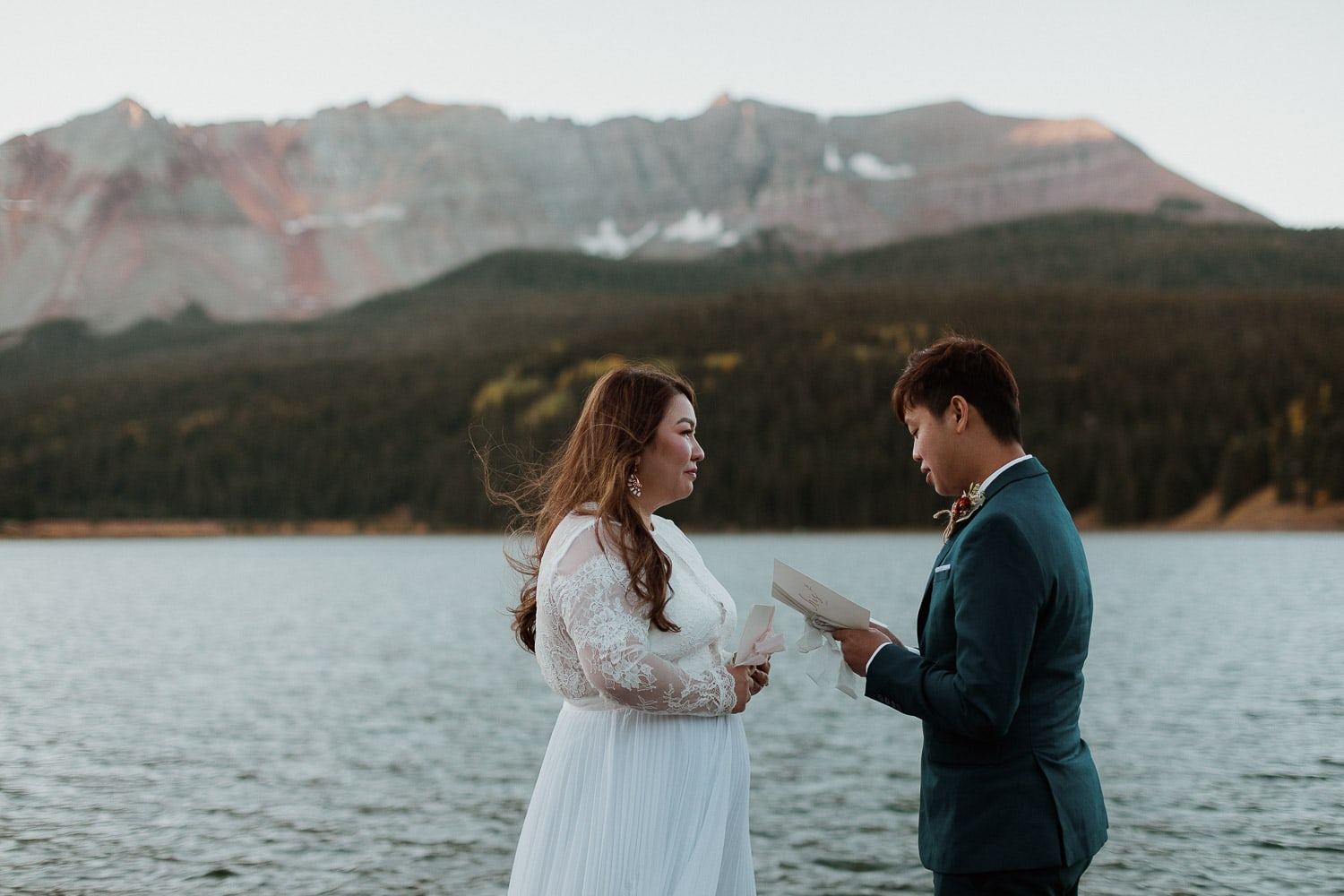 groom reads out loud vows during ceremony at alpine lake