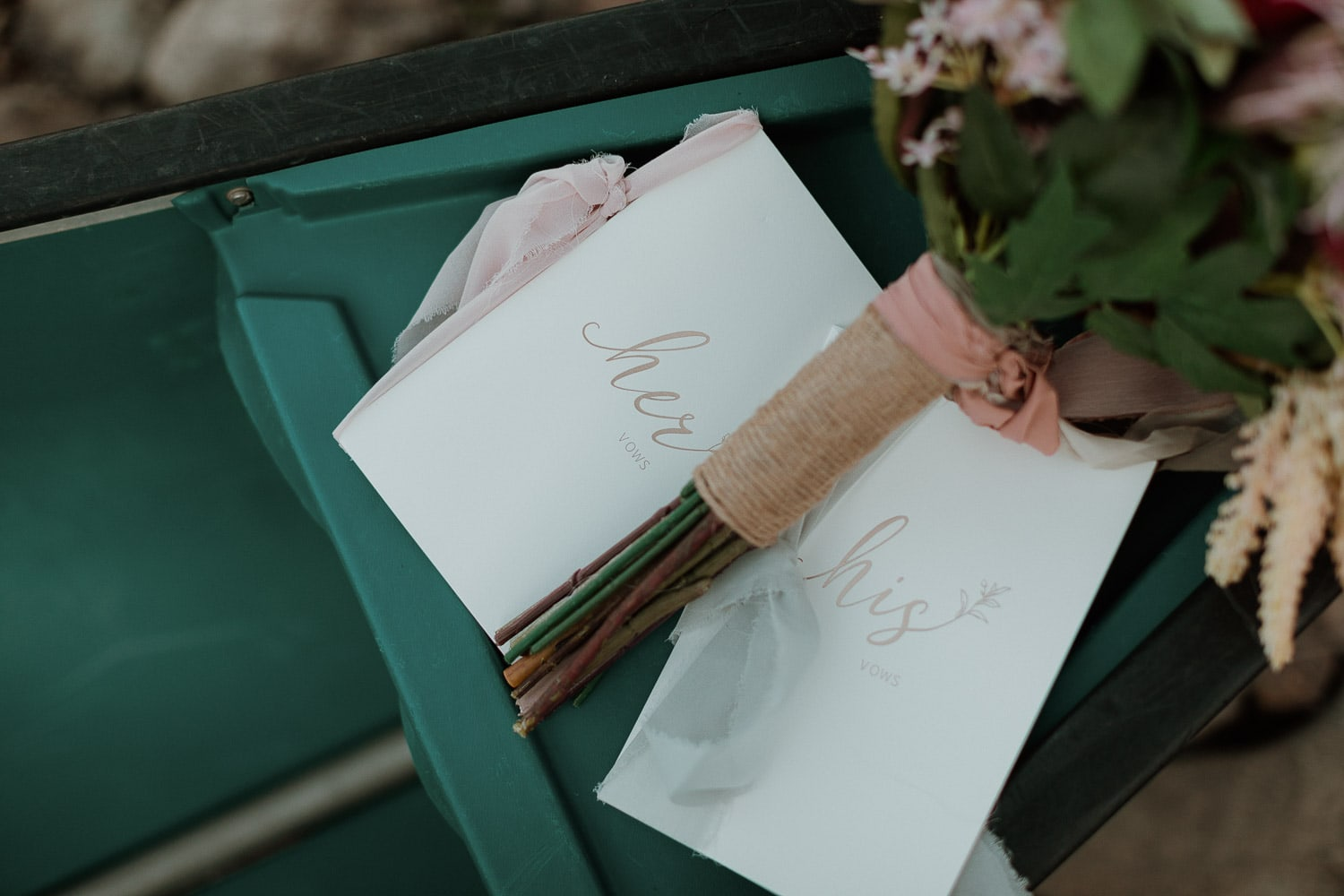 vow books in styled elopement photo with floral arrangement