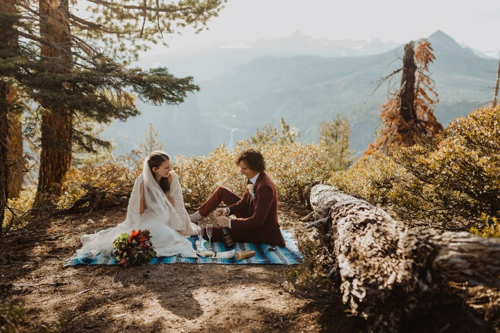 couple having a picnic overlooking valley and waterfall