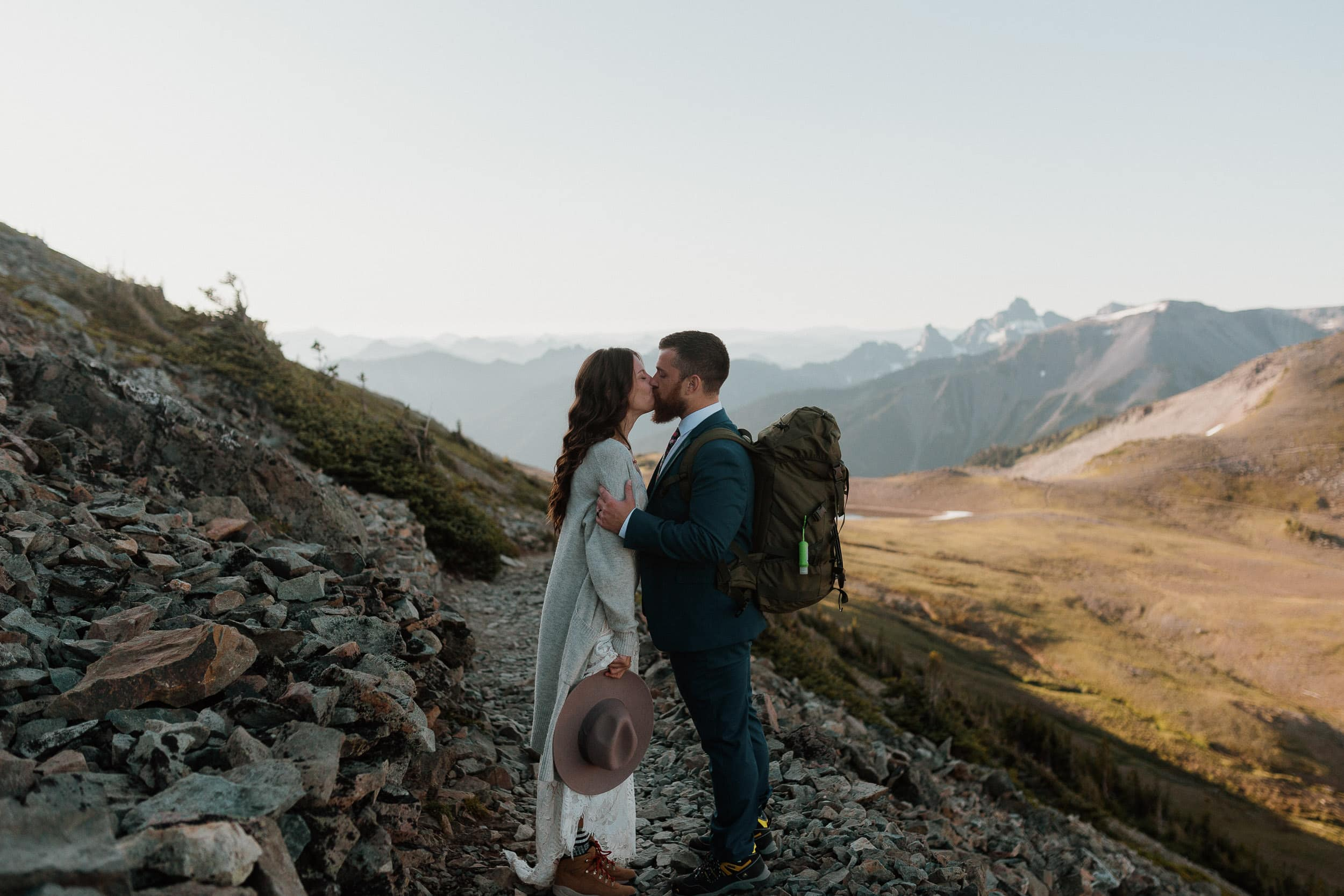 couple kissing on hiking trail with views of mountain range