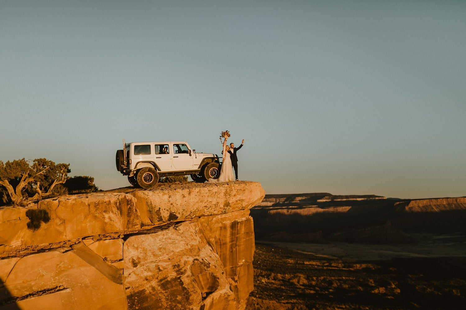 bride and groom celebrate on cliff edge for sunset with jeep