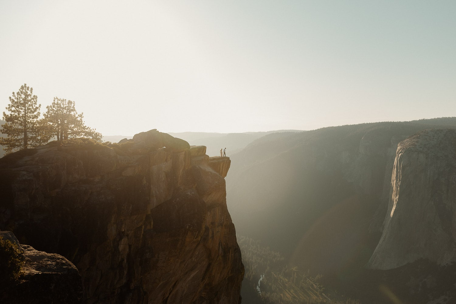 couple standing at edge of cliff at sunset