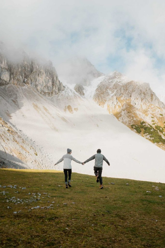 couple skipping holding hands towards snowy mountain