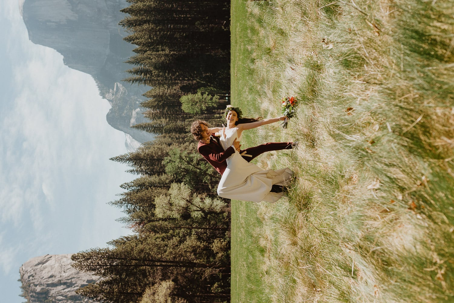 groom dipping his bride down in celebration in a meadow