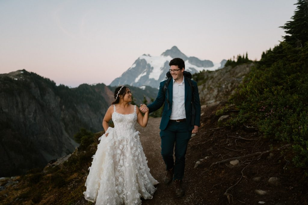 Bride and groom hiking in the mountains at sunset