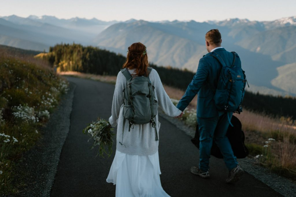 Bride and groom hiking in Washington with daypacks during elopement