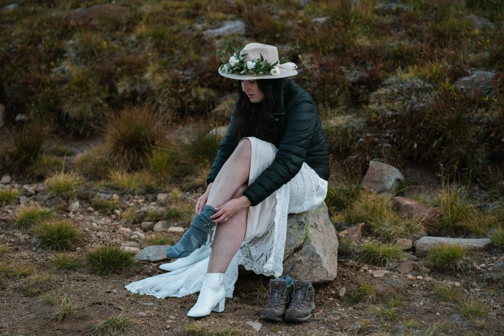 Bride putting on socks and hiking boots before elopement ceremony in the Rocky Mountains of Colorado