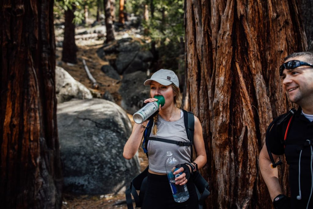 elopement guest using oxygen while hiking in the forest