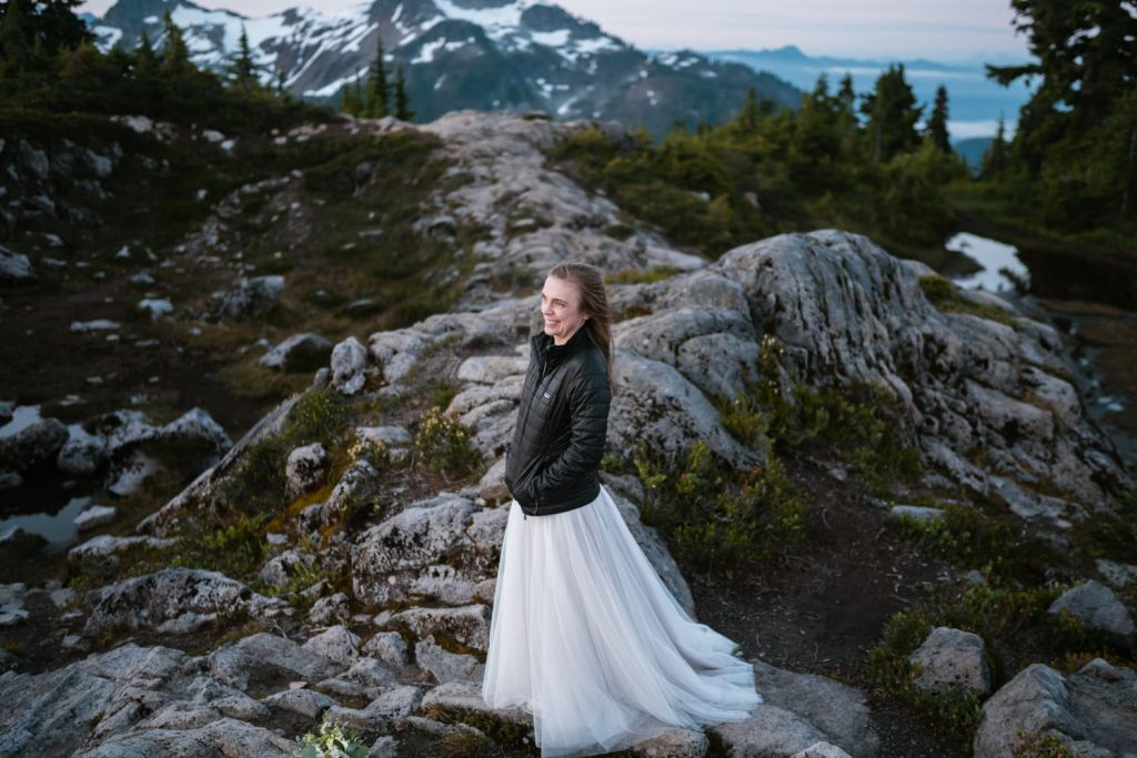 bride wearing down jacket at sunrise on a hiking trail in the washington mountains