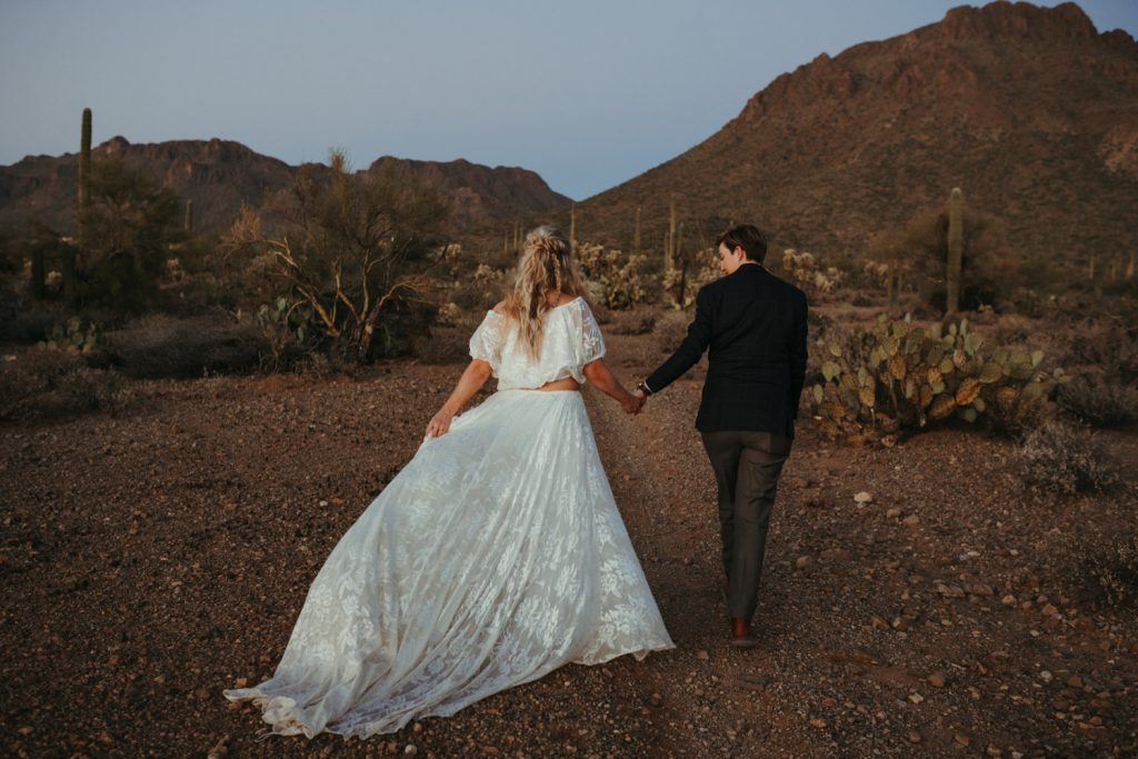 Couples hiking in the desert at sunset with elopement dress swaying on the trail