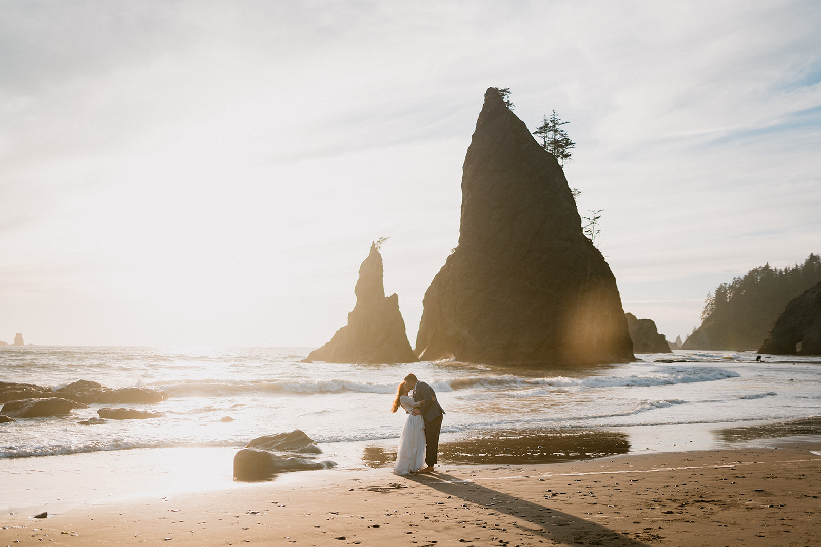 Couple eloping at sunset at Rialto Beach with rock formations in the distance