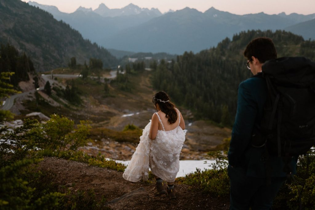 couple hiking in Washington mountains while bride holds up her elopement dress