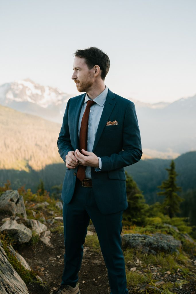 Groom wearing navy elopement suit in the mountains at sunset