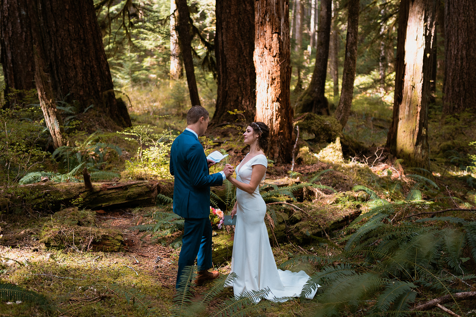 groom reading vows in forest